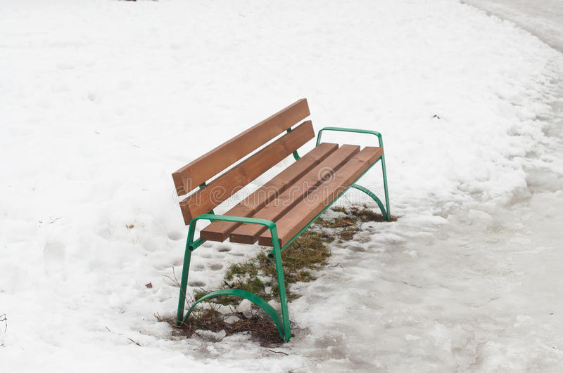 Bench on melted snow royalty free stock images