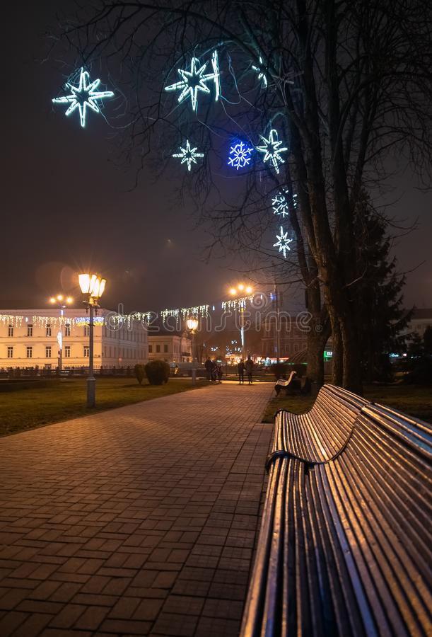 Bench in misty city park at night. By the light of street lamps. Natural winter autumn background stock photography