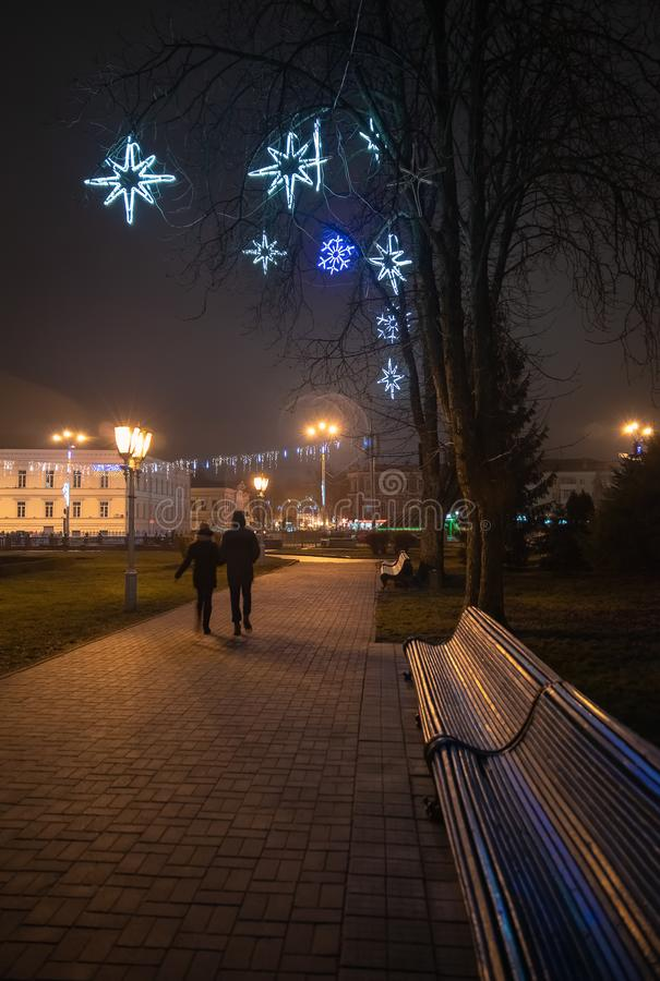 Bench in misty city park at night. By the light of street lamps. Natural winter autumn background stock images