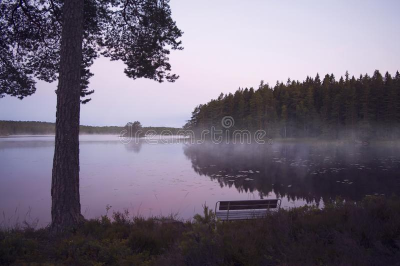 Bench by misty lake in beautiful sunrise. An empty bench facing a lake by a beautiful, colorful, summer sunrise. Fog sweeping over the surface. Värmland stock photos