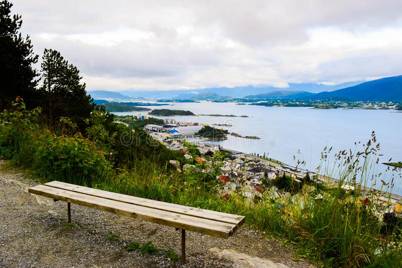 Bench on the mountain Aksla at the Alesund cityscape background whit architecture of city in Art Nouveau, Neoclassical and neo-. Gothic  style. Sun rays royalty free stock images