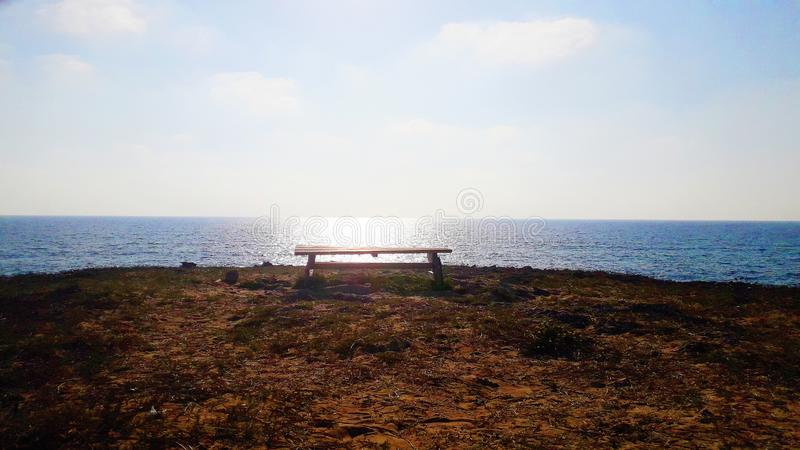 A bench overlooking the horizon stock image