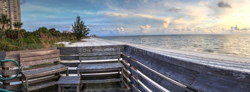 Bench overlooks the ocean at Vanderbilt Beach at sunset. In Naples, Florida royalty free stock photo
