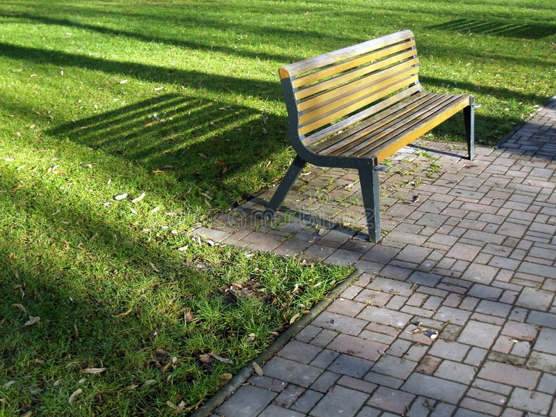 Bench in a park. Casting very long shadows at late afternoon stock photo