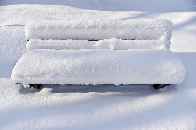 Bench in a park covered completely by snow royalty free stock images