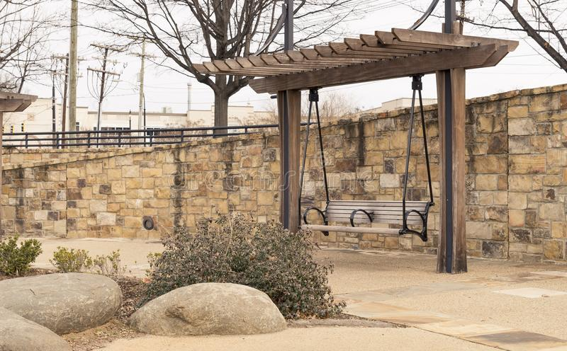 Bench pergola in park alongside stone brick wall on gravel walkway stock images