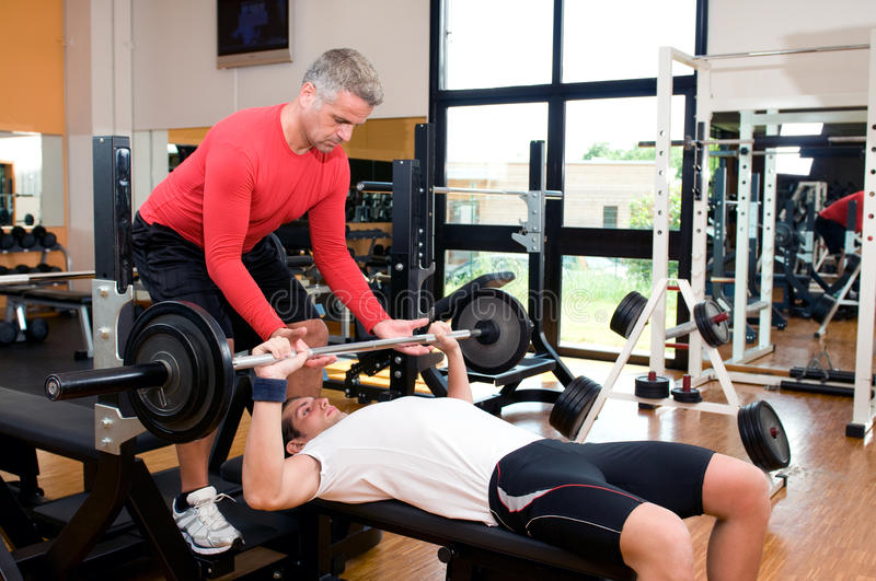 Bench press at gym. Young man doing weigths on a bench press with the help of the mature instructor at gym royalty free stock photography