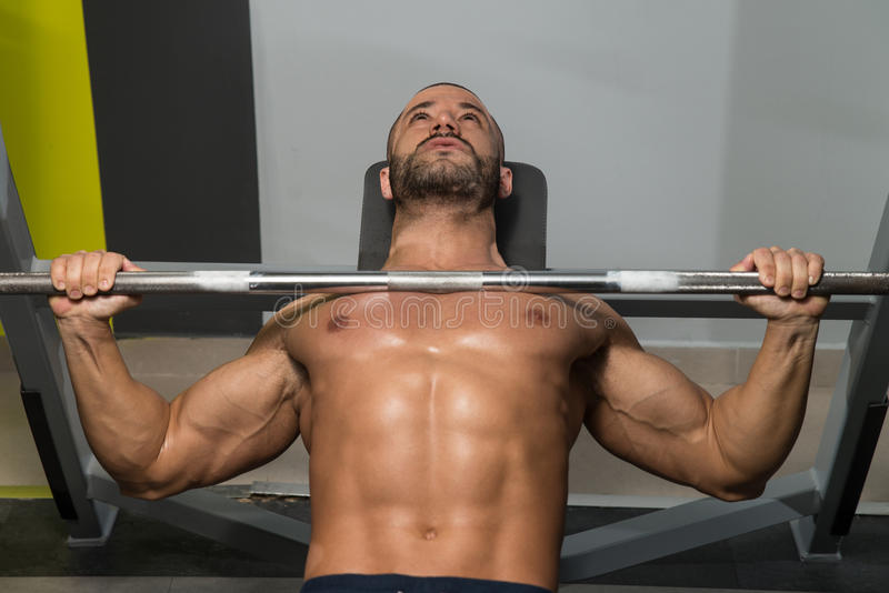 Bench Press Workout. Young Man In Gym Exercising Chest On The Bench Press stock images