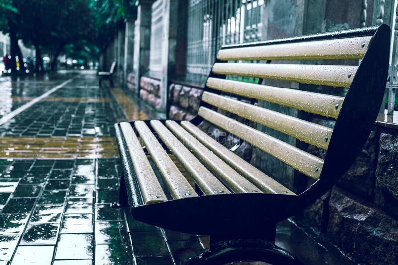 Bench in rain stock photos