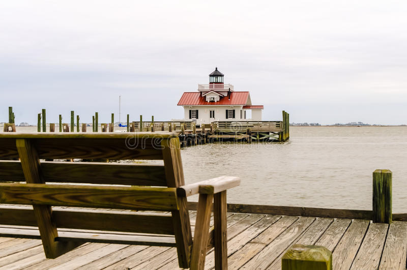 Bench at roanoke marshes lighthouse. A bench in front of roanoke marshes lighthouse stock photo