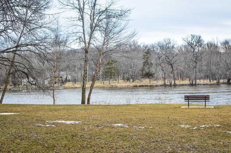 Bench by Rock River - Riverside Park - Janesville, WI royalty free stock photography