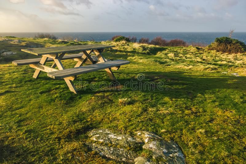 Bench on a rocky shore during a sunset stock images