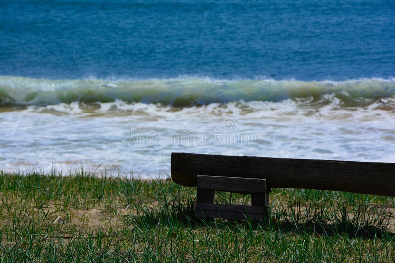 Bench on sea shore royalty free stock photography