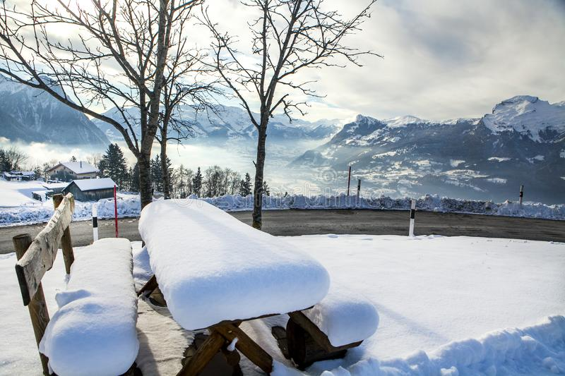 Bench in the snow overlooking the Alps in winter on a Sunny day stock image