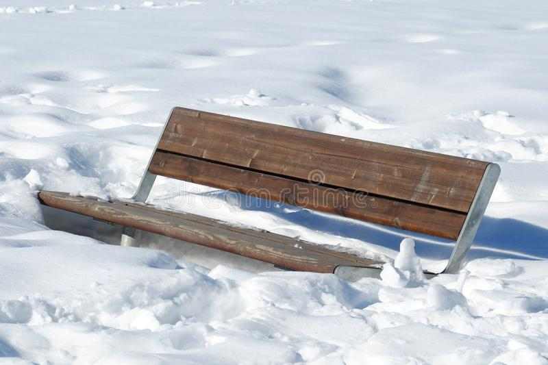 A bench in the snow in the park stock image