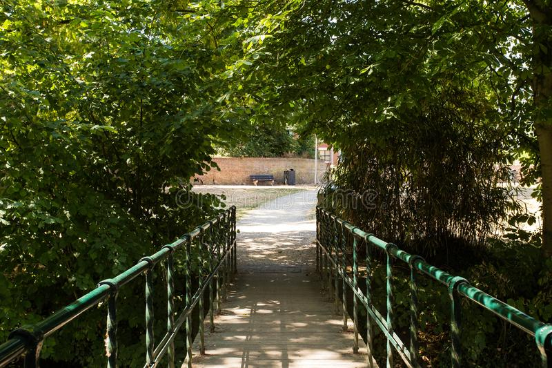 Bench in the summer park with old trees and wooden bridge. With sunlight stock images