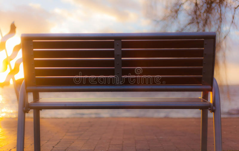 Bench in sun. Bench by the water in the sun stock photography
