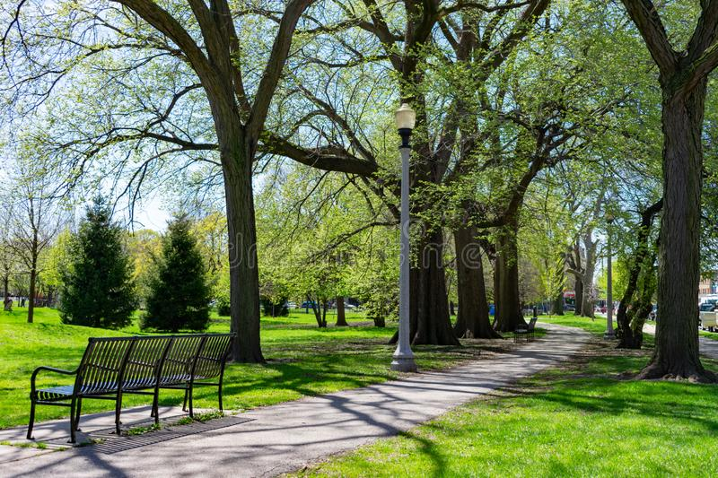 Bench and Trail at Welles Park in Lincoln Square Chicago. A bench next to a paved path in front of green grass and trees at Welles Park in the Lincoln Square stock photos