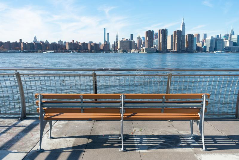Bench vazio em um parque em Greenpoint Brooklyn Nova York olhando em direção ao East River e à linha do horizonte de Manhattan fotografia de stock royalty free