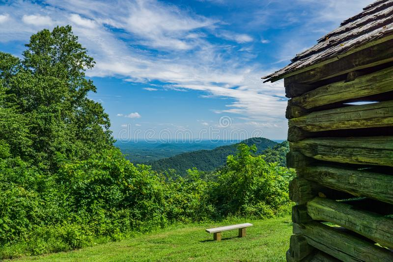 A Bench With A View and a Log Cabin. A bench with an outstanding view of the valley below and the blue sky above located off the Blue Ridge Parkway in Floyd royalty free stock images