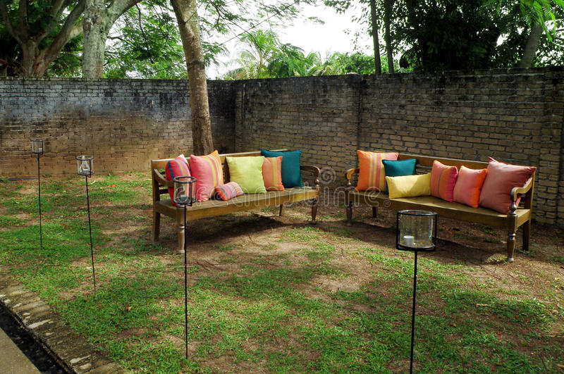 Benches with cushions in garden. A photograph image of a corner of a sunny tropical garden with long wooden benches decorated with colorful cushions in various stock photo