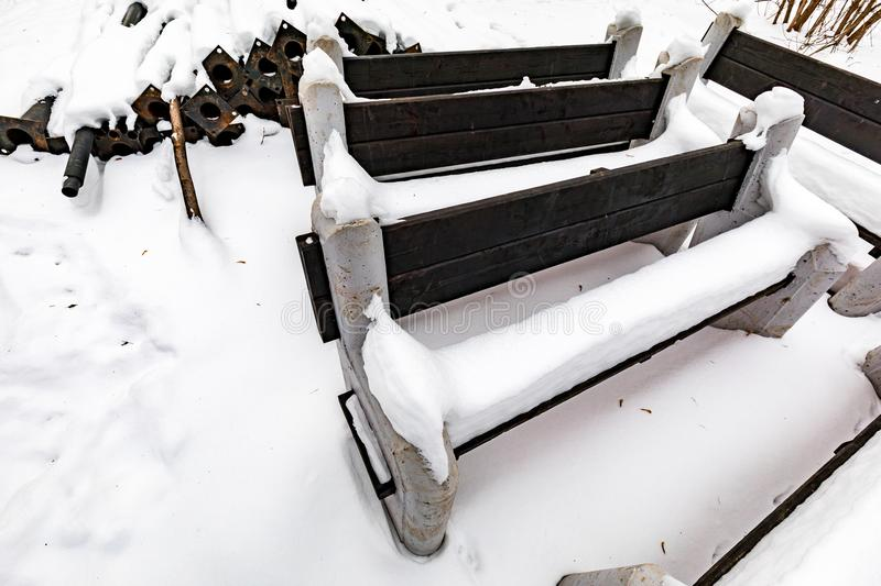 Benches made of wood and concrete covered with snow in the park. stock photography