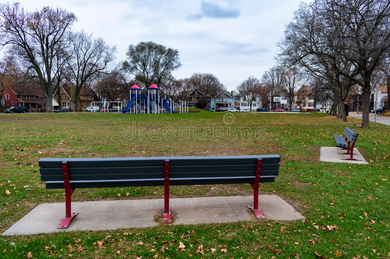Benches at a Park in Madison Wisconsin during a Cold and Overcast Autumn Day. Benches at a park with open green space and surrounded by homes in Madison royalty free stock photos
