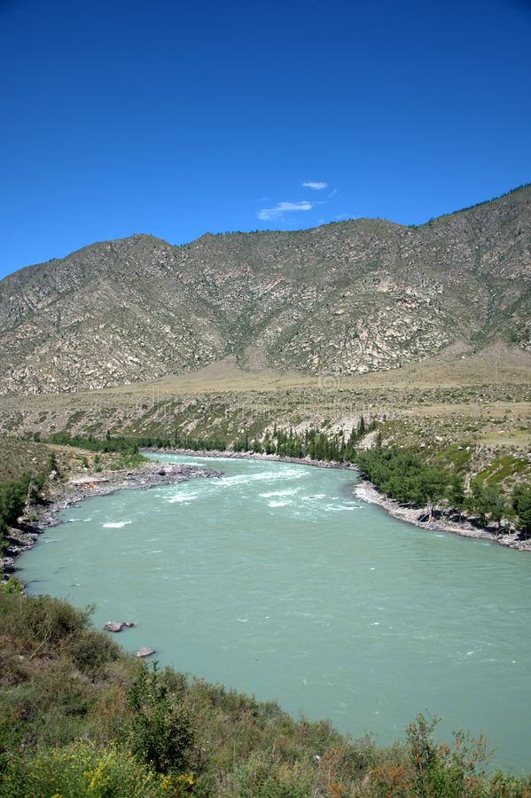The bend of the channel of a mountain river of turquoise color in a valley lying at the foot of high rocky hills stock images
