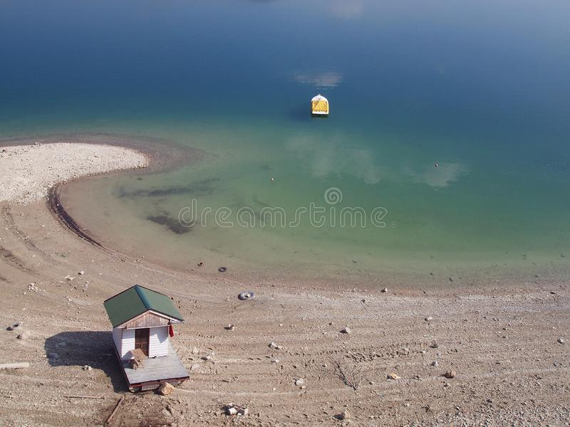 Bend of the lake, small house and boat. stock photo