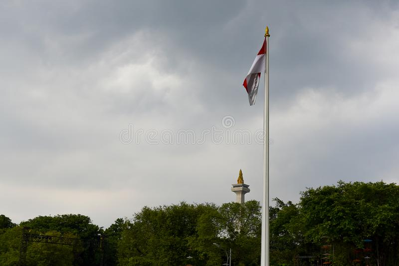 The Red and White Flag and the MONAS National Monument. Red and White Flag and National Monument MONAS. This historic place is located in Central Jakarta royalty free stock photography