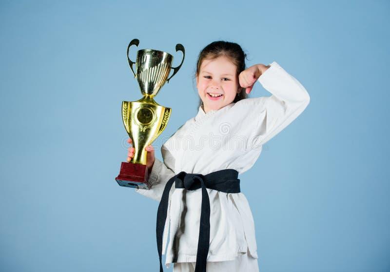 ?bendes Kung Fu Gl?ckliche Kindheit kleines M?dchen mit Meistercup chinesische KONGFU Kinder Sporterfolg im Einzelkampf sieger stockfotografie