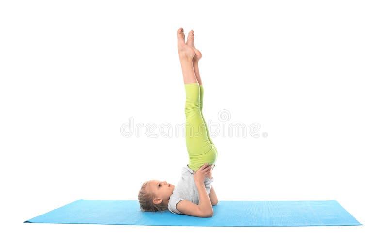 ?bendes Yoga des kleinen M?dchens auf wei?em Hintergrund stockfotografie