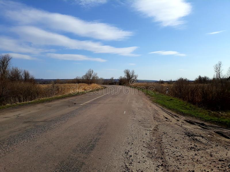 Bending asphalt road with holes royalty free stock photos