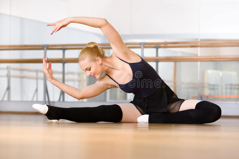 Bending ballerina stretches herself on the floor royalty free stock image