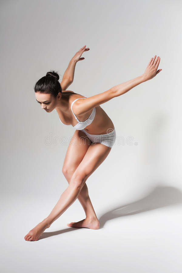 Bending ballerina in white studio stock images