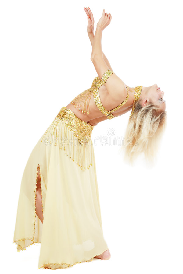 Bending belly-dancer. Beautiful blond bellydancer in golden costume dancing, over white background royalty free stock photography