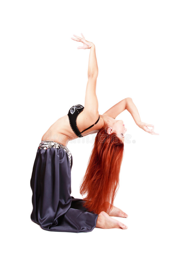 Bending bellydancer. Red-haired bellydancer in oriental costume bending on white background royalty free stock photo