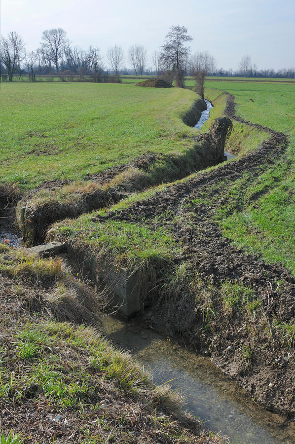 Bending ditch in winter country. Foreshortening of small ditch in winter country , shot in bright light on lombardy plains stock images