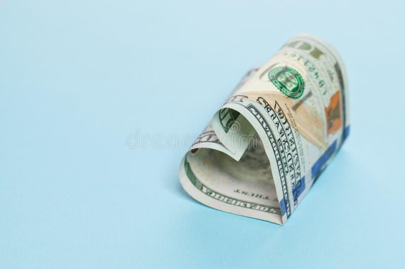 Beneficio y concepto del regalo del dinero forma del corazón del efectivo de 100 dólares americanos de la nota en fondo azul con  foto de archivo libre de regalías