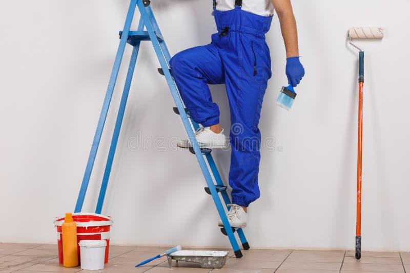 Benen av en arbetare i en overall hoppade på en högväxt trappstege som rymmer en borste arkivfoton