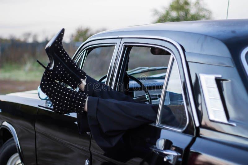 Benen av flickan i kängor med häl synliga i fönstret av bilen royaltyfri foto