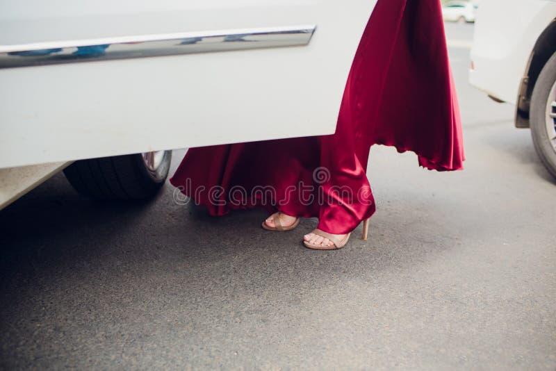 Benen die van meisje van oude auto weggaan jonge vrouw in hoge hielenschoenen Chauffeur openingsdeur van uitstekende auto voor stock fotografie