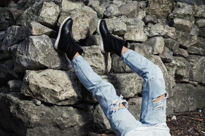 Benen gekleed in gescheurde blauwe jeanswith zwarte modieuze laarzen Studiofoto op de achtergrond van de rotsmuur stock afbeeldingen