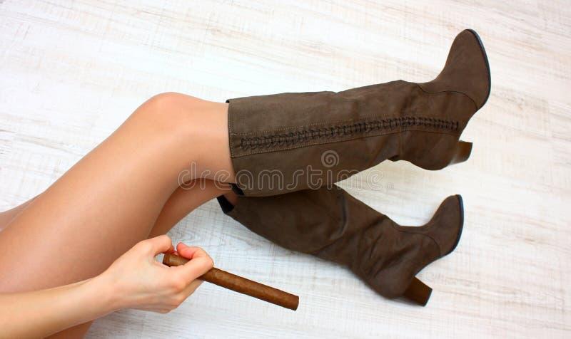 Benen, laarzen, en sigaar stock fotografie