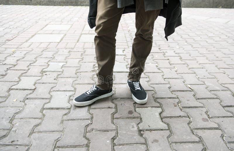 Benen in smalle zwarte tennisschoenen stock foto's