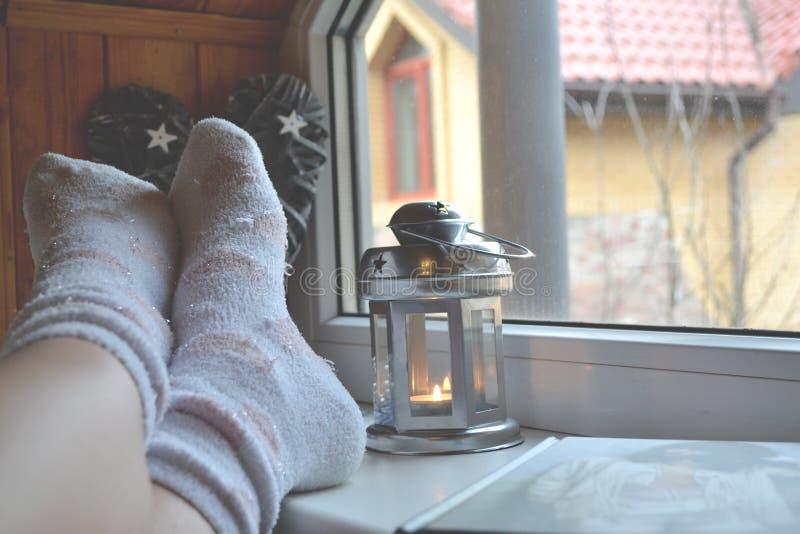 Benen in sokken Vrouw het ontspannen thuis dichtbij het venster Decor in de woonkamer stock afbeelding