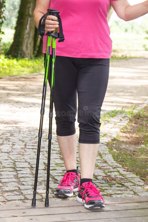 Benen van bejaarde hogere vrouw en noordse wandelstokken, sportieve levensstijlen stock afbeelding