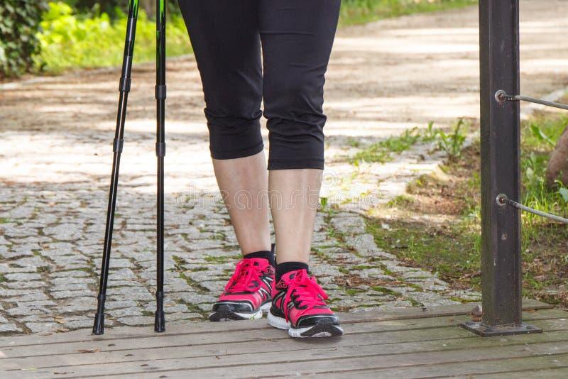 Benen van bejaarde hogere vrouw en noordse wandelstokken, sportieve levensstijlen royalty-vrije stock afbeeldingen