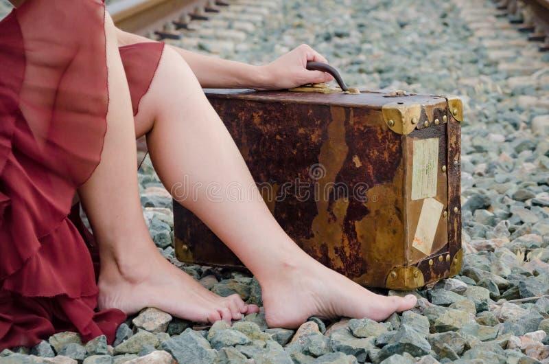 Benen van blootvoetse vrouw met oude koffer op het treinspoor royalty-vrije stock foto's