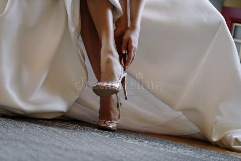 Benen van de bruid in elegante schoenen stock foto's
